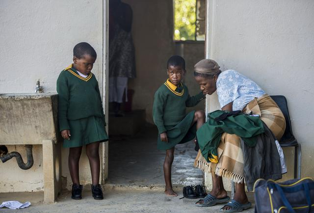 Sisters at Mants'ase Children's Home in Mohale's Hoek, Lesotho, are assisted by a house mother as they prepare to walk to school.